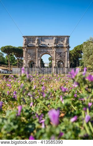 Arch of Titus or Arco di Tito in Rome, Italy. Historical landmark of Rome. Ancient ruins of Triumph arch with flowers at foreground