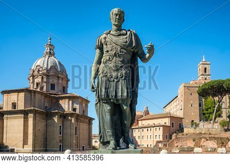 Ancient statue of Julius Caesar in Rome with Santi Luca e Martina church at background, Italy