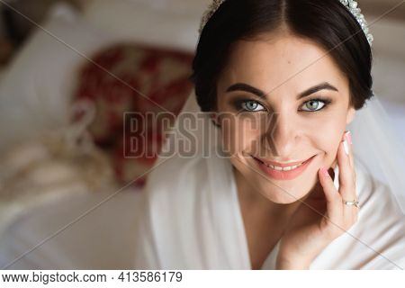 Portrait Of Beautiful Bride With Fashion Veil Posing On Bed At Wedding Morning. Makeup. Brunette Gir