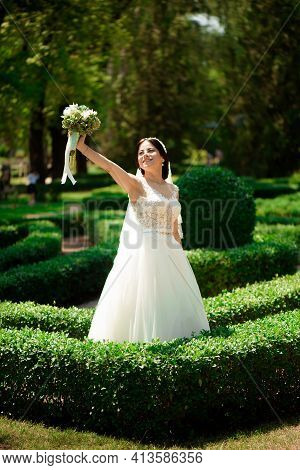 Beautiful Bride With Wedding Flowers Bouquet, Attractive Woman In Wedding Dress. Happy Newlywed Woma