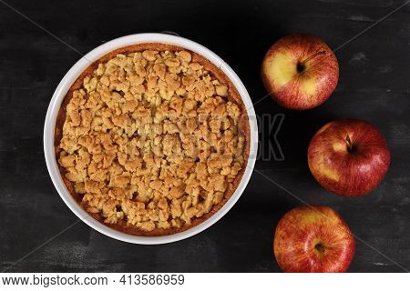 Top View Of Whole Traditional European Apple Pie With Topping Crumbles In White Springform Pan On Da