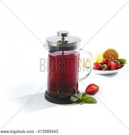 Tea in French Press on White Background. Homemade Tea with Berry and Green Herbs. Isolated over White