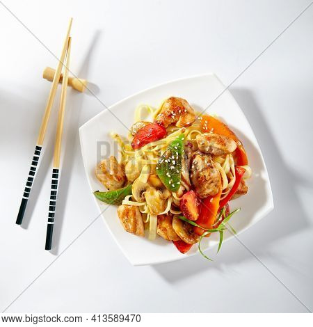 Udon noodles with sweet and sour chicken and vegetable. Asian style noodles food on white background. Udon in white plate with wooden choopsticks. Top view