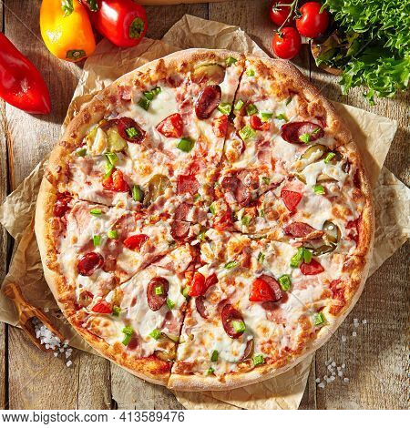 Pizza restaurant menu - Meat Pizza on parchment, topped off with meat hot sausage and pepperoni slice. Wooden table with pizza ingredients. Sunlight with harsh shadow. Rustic, natural style food