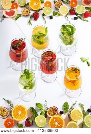 Summer fruit lemonade on white background. Fresh summer drink with fruit frame on white table. Lemonades ingredients frame - citrus fruit, berries and herbs