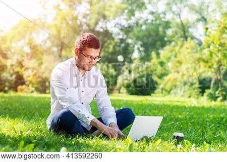 Young Businessman Sitting On Green Grass And Using Laptop Computer. Handsome Man Working With Comput