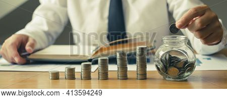 Man's Hand. Put A Coin Into A Glass Bottle With Coins, Saving Money With Coins, Stepping Into A Succ