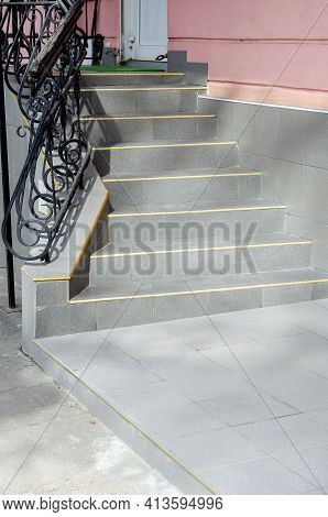 Steps And Metal Railings. Staircase With Gray Steps And Wrought Iron Railings. Entrance To The Pink