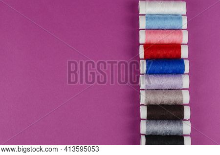 Multicolored Reels Of Thread On A Purple Background. Thread Set In Line. Top View, Flat Lay. Copy Sp
