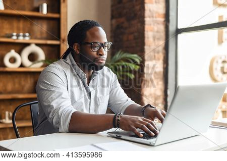 Busy Bored Young African-american Male Author Office Worker In Glasses Sitting At The Desk Typing On