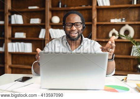 Happy Young African-american Office Worker In Glasses And Headset Looking At Laptop Screen And Gestu