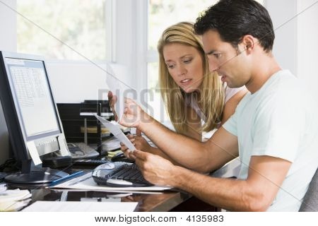 Couples In Home Office With Computer And Paperwork Looking Unhappy