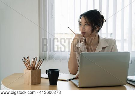 Portrait Of Business Asian Woman Thinking And Working With Laptop Computer In Office