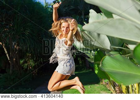 Happy Young Woman Have Fun On Tropical Resort. In Luxury Villa Garden Funny Girl Jumping High Show T