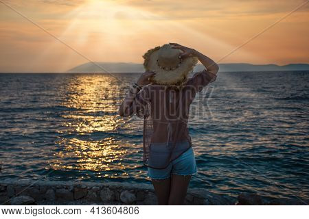 Woman In Straw Hat And Shorts By The Sea Looks At The Sunset