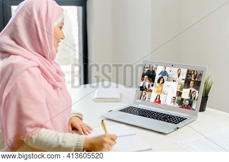 Young Muslim Arab Woman With Laptop Working Studying Remotely From Home, Taking Notes, Meeting Onlin
