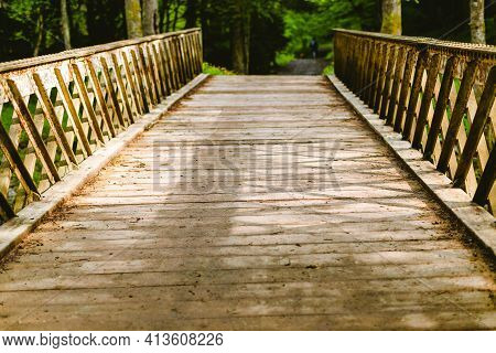 Landscape Photo Of Wooden Bridge Path Over The Forest Stream On Sunrise Spring Morning. Beautiful Su