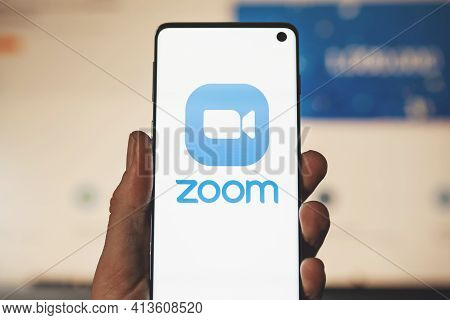 Swansea, Uk - March 18, 2021: Man Holding A Smartphone With Zoom App Logo With Blurred Website Backg
