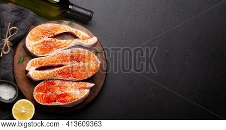 Fresh raw salmon cooking. Fish steaks with herbs, spices and white wine. Top view flat lay with copy space