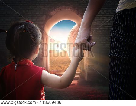 Child's Hand Holding Mother's Finger On Blurred The Cross Of Jesus Christ Background.