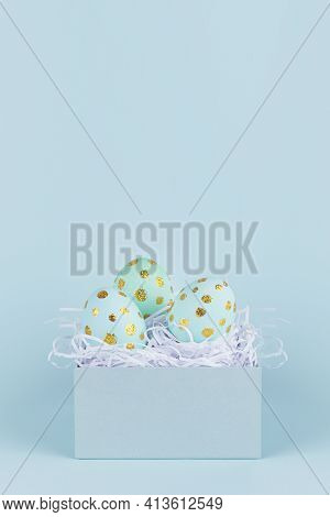 Simplicity And Minimal Design Of Easter Eggs With Gold In Gift Box On Blue Background, Vertical.