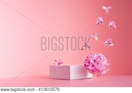 White Square Podium For Display Cosmetic And Goods With Hovering Flow Of Fresh Spring Flowers  On Ge