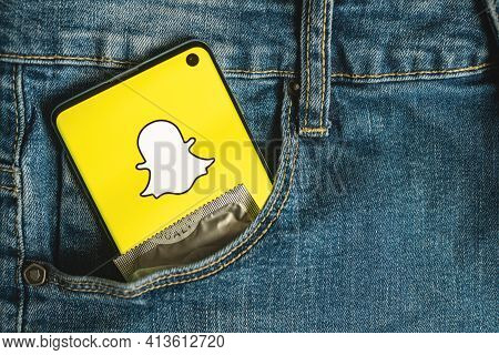 Smartphone With Snapchat App Logo With Condom In Blue Jeans Pocket