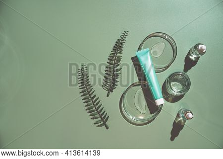 Different Glass Bottles With Serum Or Oil And Cosmetic Skin Care Cream On Green Background. Trending