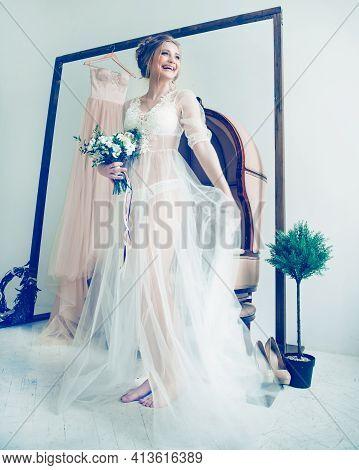 Happy Bride In Boudoir Dress Standing In Spacious Hotel Room