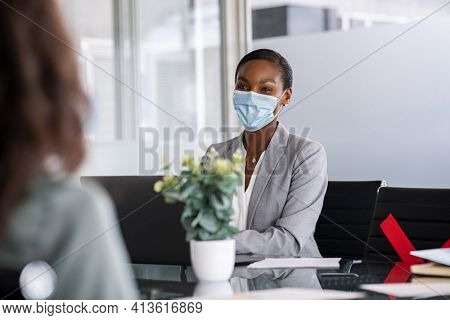 Mature african american businesswoman working in office while wearing face mask due to Covid. Successful smiling woman with surgical face mask taking interview of applicants keeping social distancing.