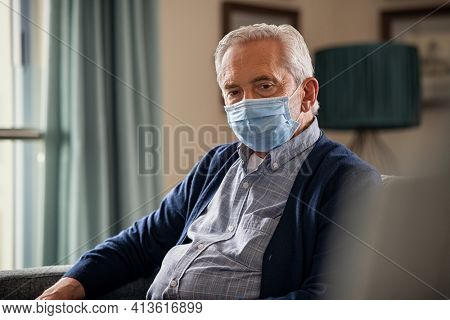 Portrait of old man wearing surgical face maskfor safety against covid-19 sitting alone at home. Depressed lonely senior man with protective mask sitting on sofa during lockdown. Sad elder at home.