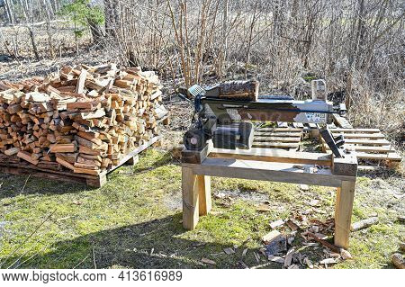 Electric Wood Splitter Standing Infront Of Firewood