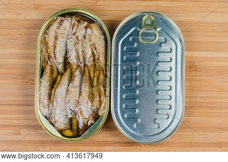Smoked Canned Sprats In Cooking Oil In Open Tin Can And Sealed Tin Can On A Wooden Surface, Top View