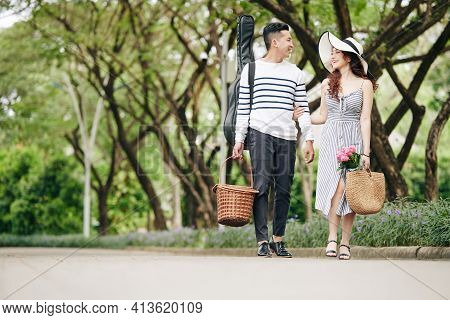 Happy Young Vietnamese Couple With Guitar And Basket Of Food Walking In Park