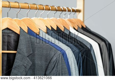 Mens Suits In Different Colors Hanging On Hanger In A Retail Clothes Store, Close-up. Mens Shirts, S