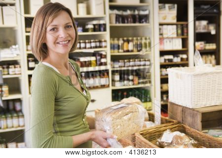Woman In Market Looking At Bread Smiling