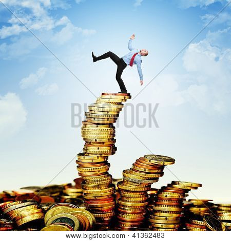 worker is going to fall from euro coin pile