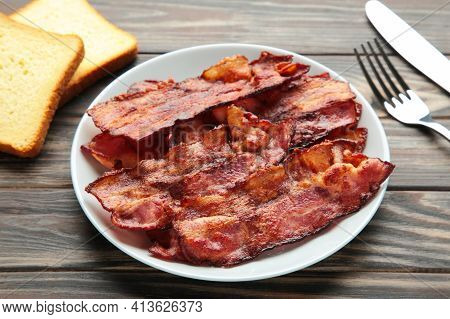 Bacon Fried Slices In Plate On Brown Background.