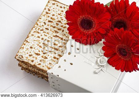 Passover Background With Matzo And Red Gerberas. Jewish Holiday. View From Above. Passover (passover