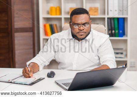 Freelance designer workplace at home office. Young African-American man works using a computer, graphics tablet and other devices. Remote job.