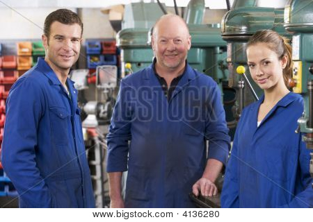 Three Machinists In Workspace By Machine Talking