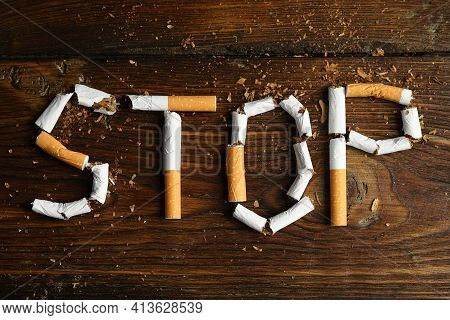 Word Stop Of Cut Cigarettes On Wooden Table, Flat Lay. Quitting Smoking Concept
