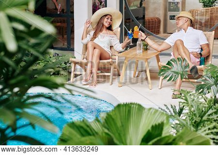 Happy Young Couple Toasting With Cocktail Glasses When Relaxing In Chaise-lounges By Swimming Pool O