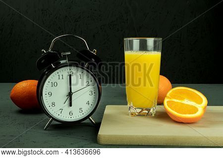 Alarm Clock At Which Six O'clock In The Morning. Black Clock And Orange Juice. Time - 6:00 Am And Re