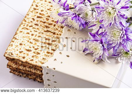 Passover background with matzah and white and purple chrysanthemums. Jewish holiday. View from above. Passover (Passover) Seder Passover celebration concept.