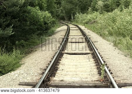 Turn Of The Railway. Steel Rails On Concrete Sleepers Disappear From View, Going Deep Into Forest Th