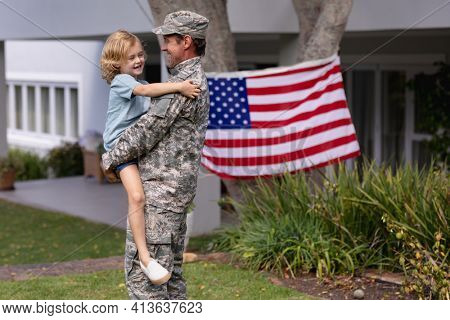 Caucasian soldier father carrying son in garden with american flag hanging outside house. soldier returning home to family.