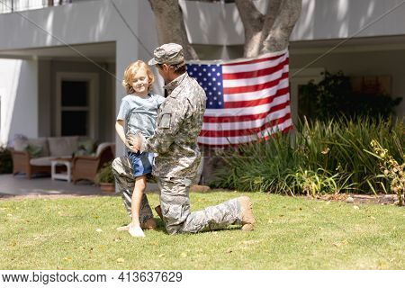 Caucasian soldier father kneeling embracing son in garden with american flag hanging outside house. soldier returning home to family.
