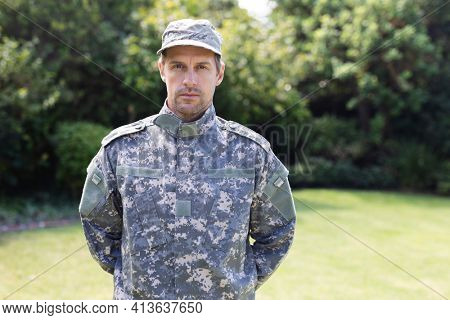 Portrait of caucasian male soldier wearing camo fatigues and cap standing in garden. soldier returning home to family.