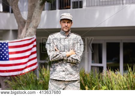 Portrait of caucasian male soldier standing in garden with american flag displayed outside house. soldier returning home to family.